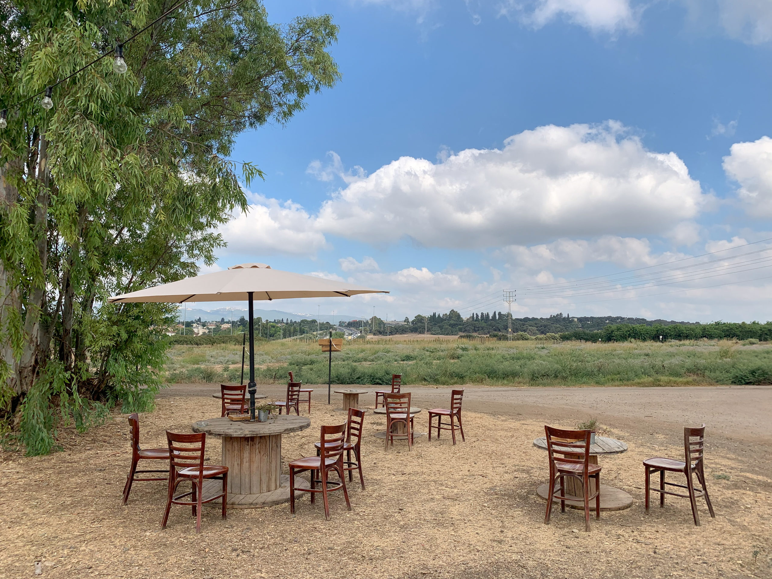 כסאות ושולחת מעץ על רקע השדות ושמיים מצויירים עם עננים לבנים בעגלת הקפה עגלולה ליד נהלל