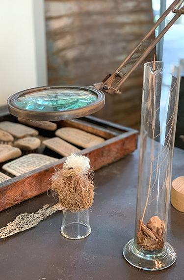 זכוכית מגדלת בוחנת חפץ בגלריית העיצוב היפה בשם בילונגינג בכפר ויתקין