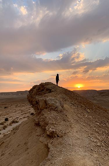 ילד עומד על צוק וצופה אל עבר השמש השוקעת מעל נחל עשוש למרגלות היישוב צוקים בערבה