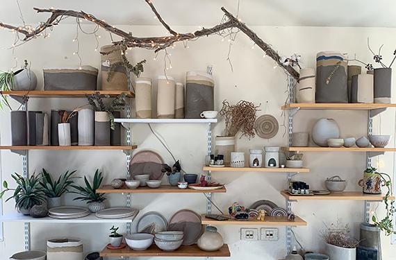 קיר עם מדפים ועליהם הכלים שיוצרת בכישרון רב רינת בר נצר בסטודיו שלה במדרשת בן גוריון