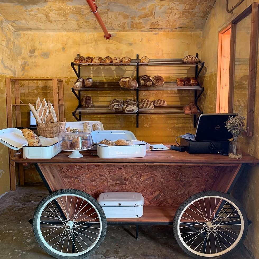 עגלה ישנה בגווני חום ומאחוריה קיר צהבהב ועליו מגוון לחמי מחמצת במאפיית ארגז לחם במושב עין ורד בשרון
