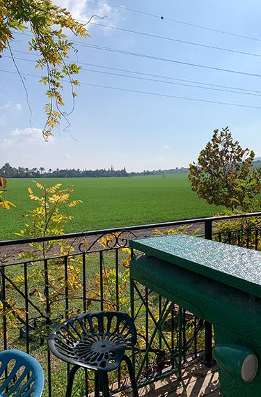כסא ושולחן מברזל צבעוני במרפסת היפה הפונה לשדות. מסעדת ארטישוק ליד בית אלפא