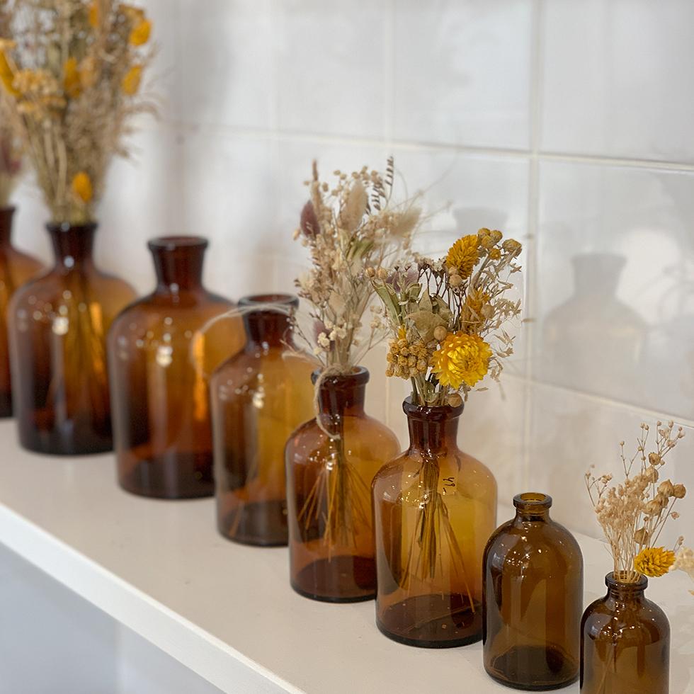 תמונה של בקבוקוני זכוכית עם פרחים יבשים בחנות הפרלמנט של עתר במתחם הרכבת בבית יהושע