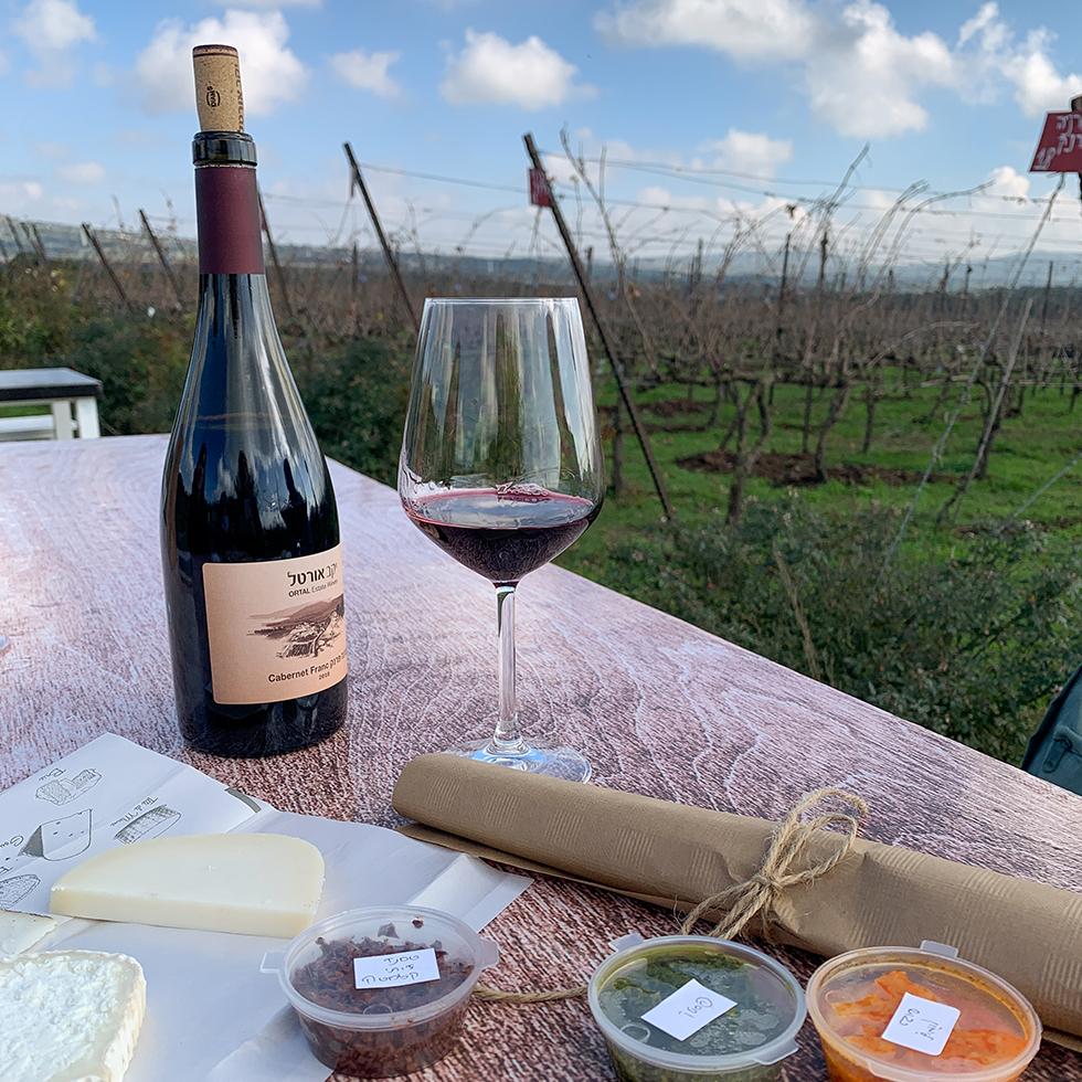 כוס ובקבוק יין, ממקחים וגבינות על השולחן הפונה לכרם ביקב אורטל ברמת הגולן