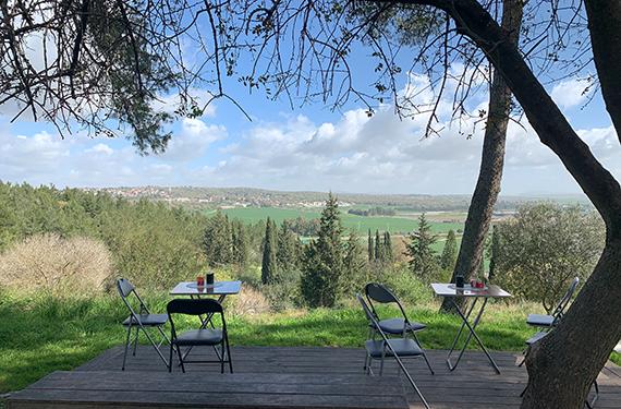 דק עם כסאות מול נוף עמק יזרעאל הנשקף מעגלת קפה על הקצה בקרית טבעון