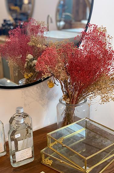 אגרטל עם פרחים יבשים על מדף ולידם מראה בחנות הרהיטים המהממת תומיק באבן יהודה