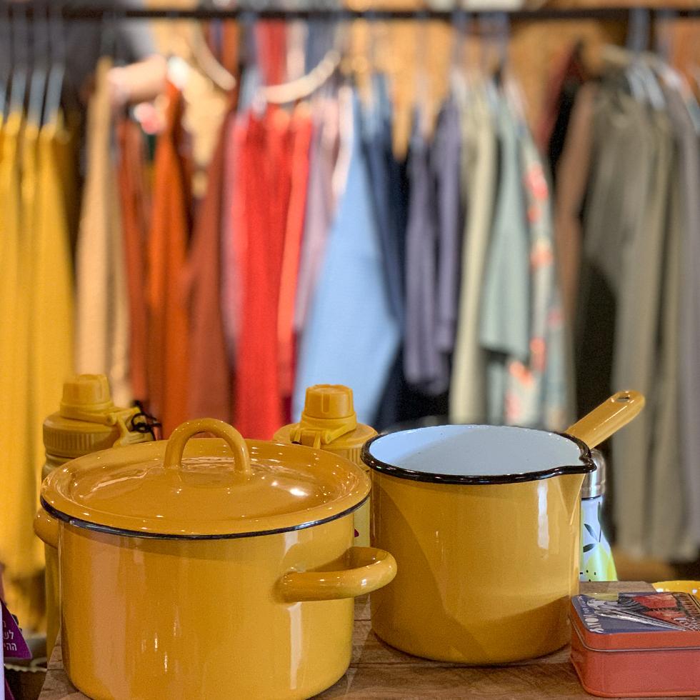 סירי אמייל צהובים ובגדים תלויים על קולב בחנות רבקה Rebecca בקיבוץ נען