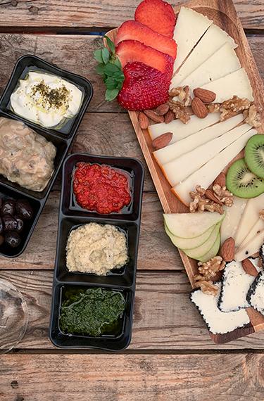 פלטת גבינות ופירות ולצידה ממרחים שונים ביקב יזרעאל בקיבוץ חנתון