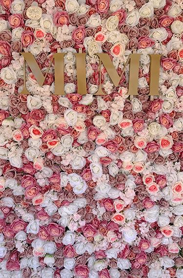 קיר פרחים ורדים מלאכותיות בוורוד ולבן וכיתוב באותיות זהב גדולות באנגלית - MIMI בכניסה לגלידריה מימי בזכרון יעקב