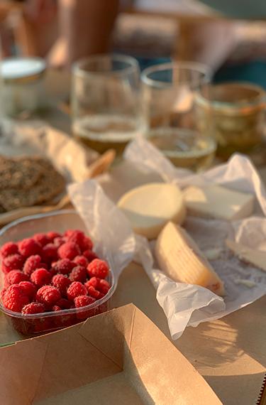 פטל אדום, גבינות וכוסות עם יין לבן ברקע בפטל ארץ - משק שגיא במושב תעוז