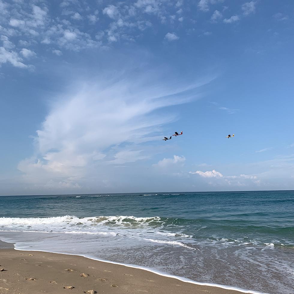 חוף פמלחים היפה עם ענן לבן ברקע וכלי טיס מעליו