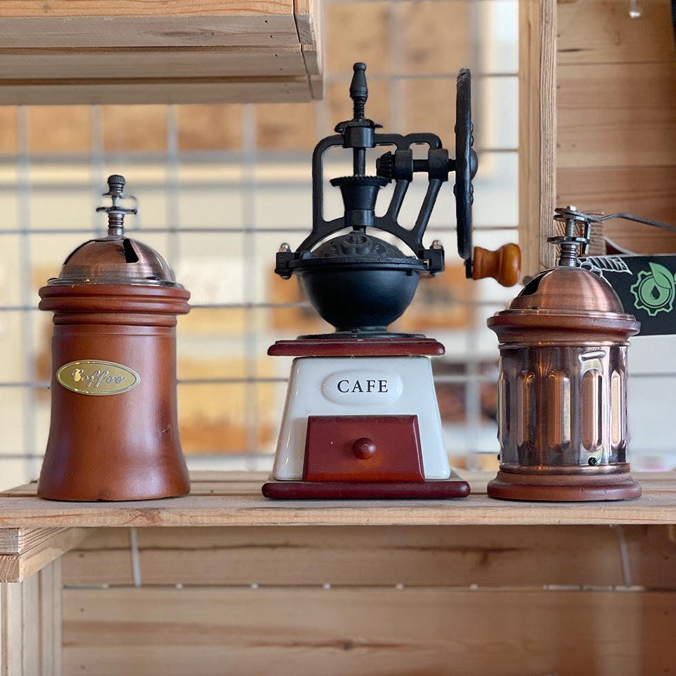 3 מטחנות ישנות בגווני חום על מדף במרכז הקפה אגרוקפה בשריגים