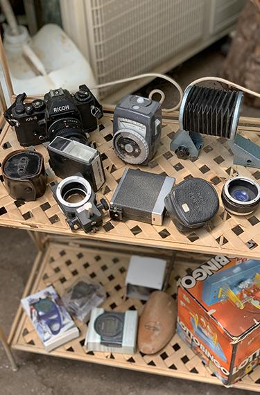 מצלמה וחלקי המצלמה ישנים מונחים על מדף באורוות האומנים בפרדס חנה