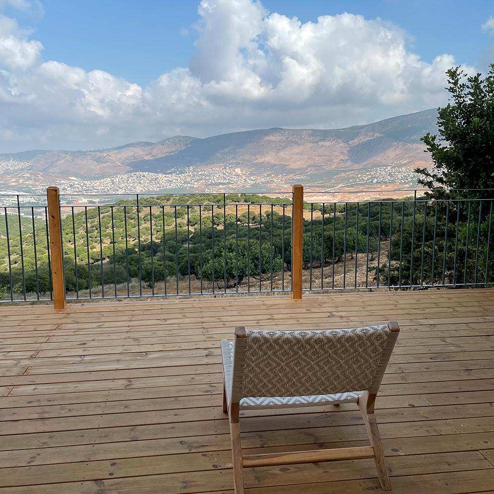 כסא על מרפסת העץ מול הנוף המטריף של הגליל בחוות רום ביישוב כמון