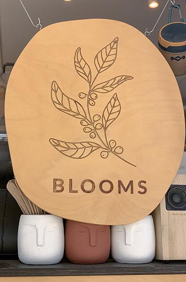 כוסות קפה ושלט מצויר מעץ ועליו הכיתוב BLOOMS בבלומס עגלת קפה בפרדס חנה