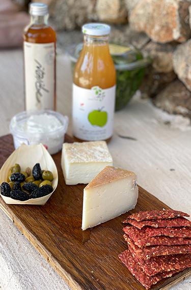 גבינות, זיתים, קרקרים, מיץ ולבנה בחוות מקורה ליד כרם מהרל